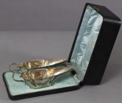 A pair of Edwardian silver sauce boats of slender octagonal form, each with cut-card rims, scroll