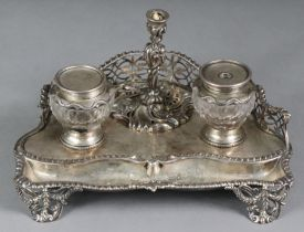 A Victorian silver inkstand of serpentine shape, with pierced gallery, fitted two glass inkwells