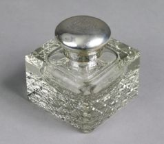 An Edwardian square glass silver-mounted inkwell with canted corners & hobnail base, the hinged