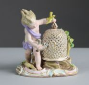 A Meissen porcelain figure of a putto, with birdcage & two birds, representing the element of Air,