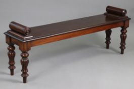 AN EARLY VICTORIAN MAHOGANY HALL BENCH, with turned bolsters to each end, on fluted baluster legs,