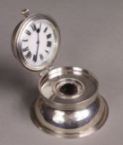 An Edwardian silver inkwell of compressed round form, the hinged lid inset timepiece to the lid