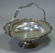 A George V silver cake basket with cut-card rim & shaped overhang handle, with engraved inscription: