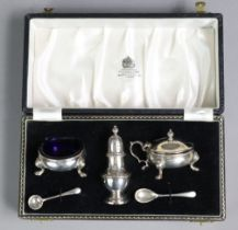 A silver three-piece condiment set comprising two squat round salts with blue glass liners & a