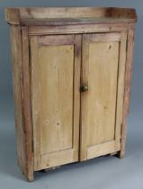 """A pine tray-top small standing cupboard, fitted two shelves enclosed by pair of panel doors, 27¾"""""""