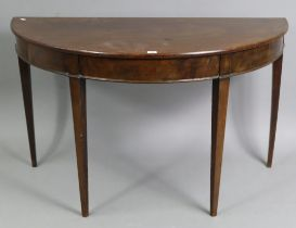 """A mahogany demi-lune console table on four square tapered legs, 44¾"""" wide x 26¾"""" high x 22¼"""" deep."""