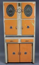 A mid-20th century white & orange painted wooden tall kitchen cabinet fitted with an arrangement