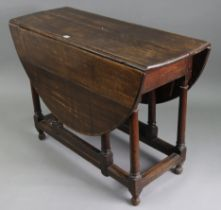 A late 19th/early 20th century oak oval gate-leg dining table, on round tapered legs & turned