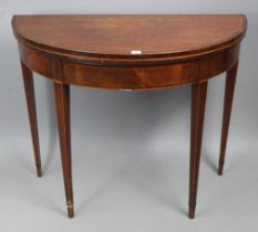 A Georgian inlaid-mahogany demi-lune tea table with fold-over top, & on four square tapered legs,