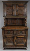 A 17th century-style carved oak tall cabinet, the upper part enclosed by a pair of panel doors above