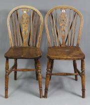 A pair of Windsor-style wheel-back dining chairs with hard seats, & on turned legs with spindle