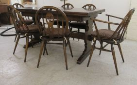 An Ercol dark oak draw leaf dining table, raised on opposing vase shaped ends and platform feet 29.