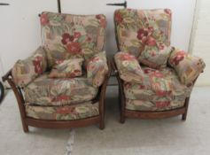 A pair of modern Ercol elm framed easy chairs with cushioned fabric upholstered backs and seats,
