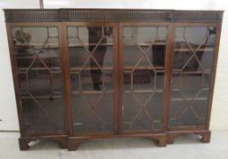 An Edwardian mahogany breakfront bookcase with a fluted frieze, over four astragal glazed doors,