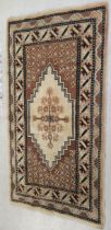 An Indian woollen rug, decorated with stylised designs,