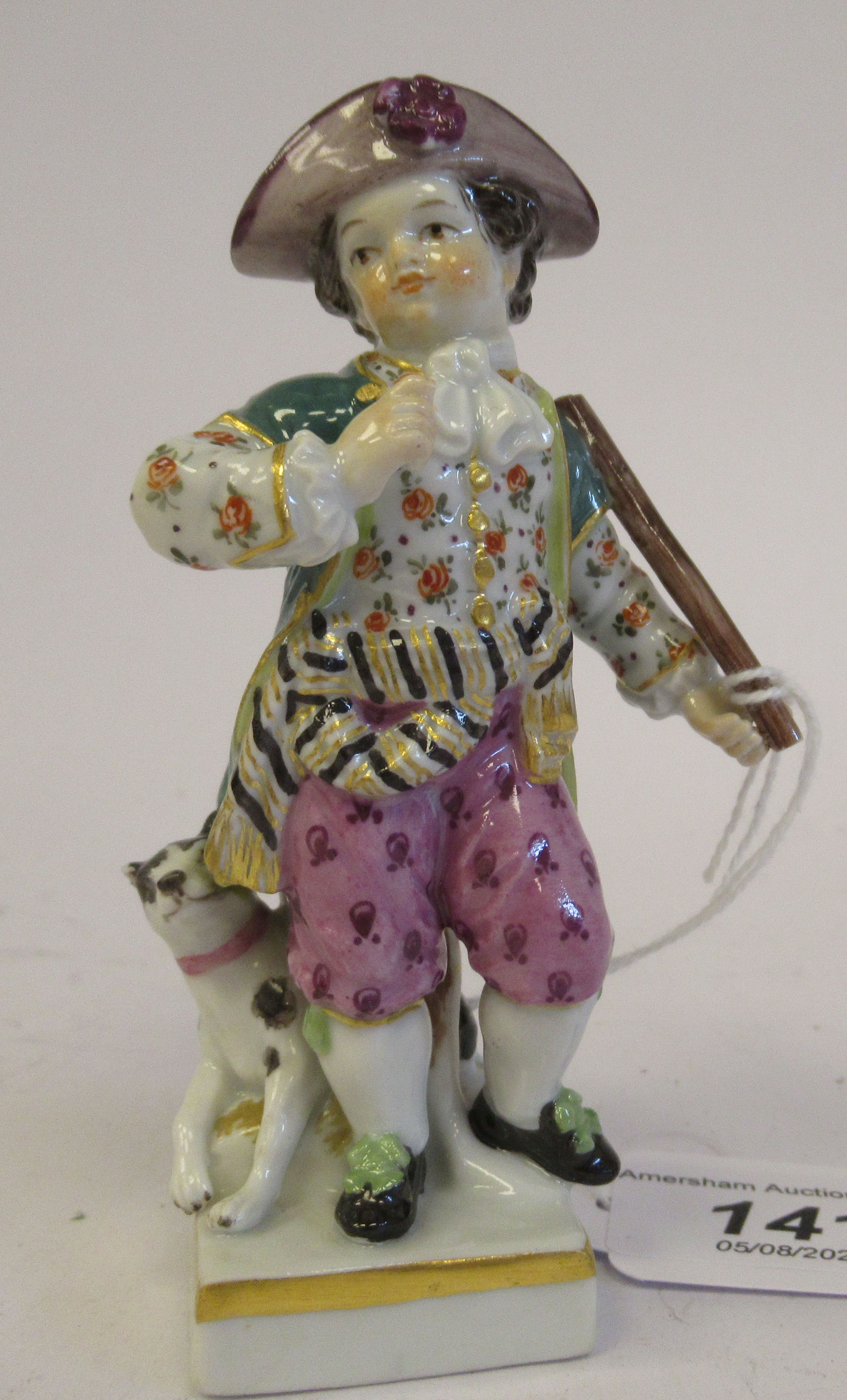 A 19th/20thC Meissen porcelain figure, a boy wearing a frock coat with a dog at his side, on a