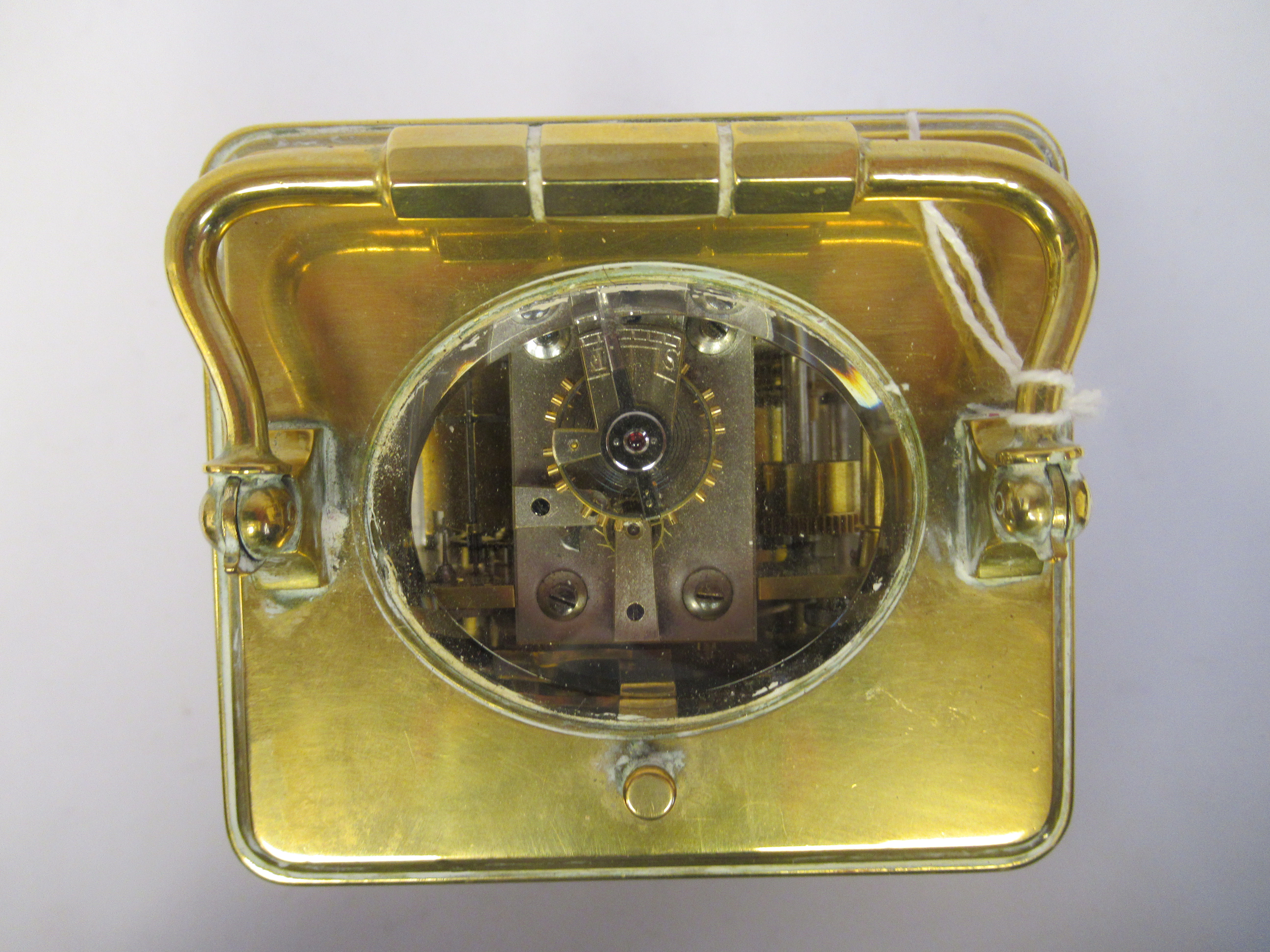 An early 20thC brass cased carriage clock with bevelled glass panels, a folding top handle, on a - Image 6 of 9