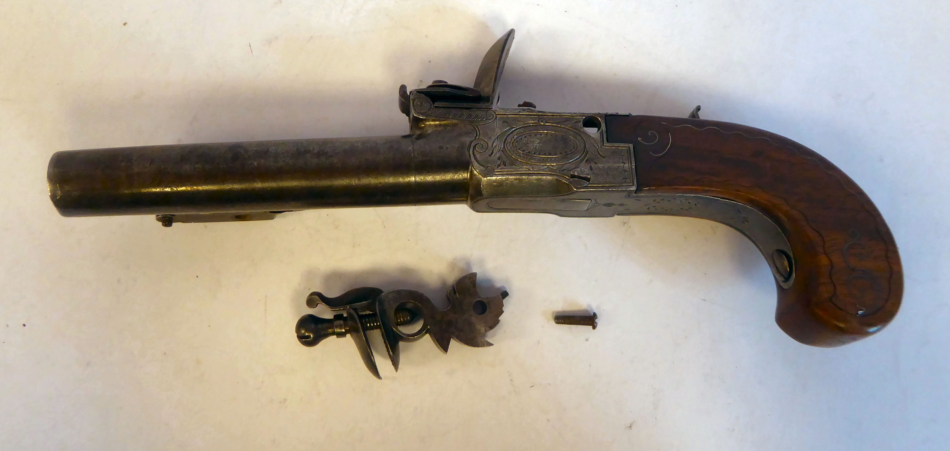 A 19thC Continental flintlock pistol with a folding trigger, inlaid wire ornament on the walnut