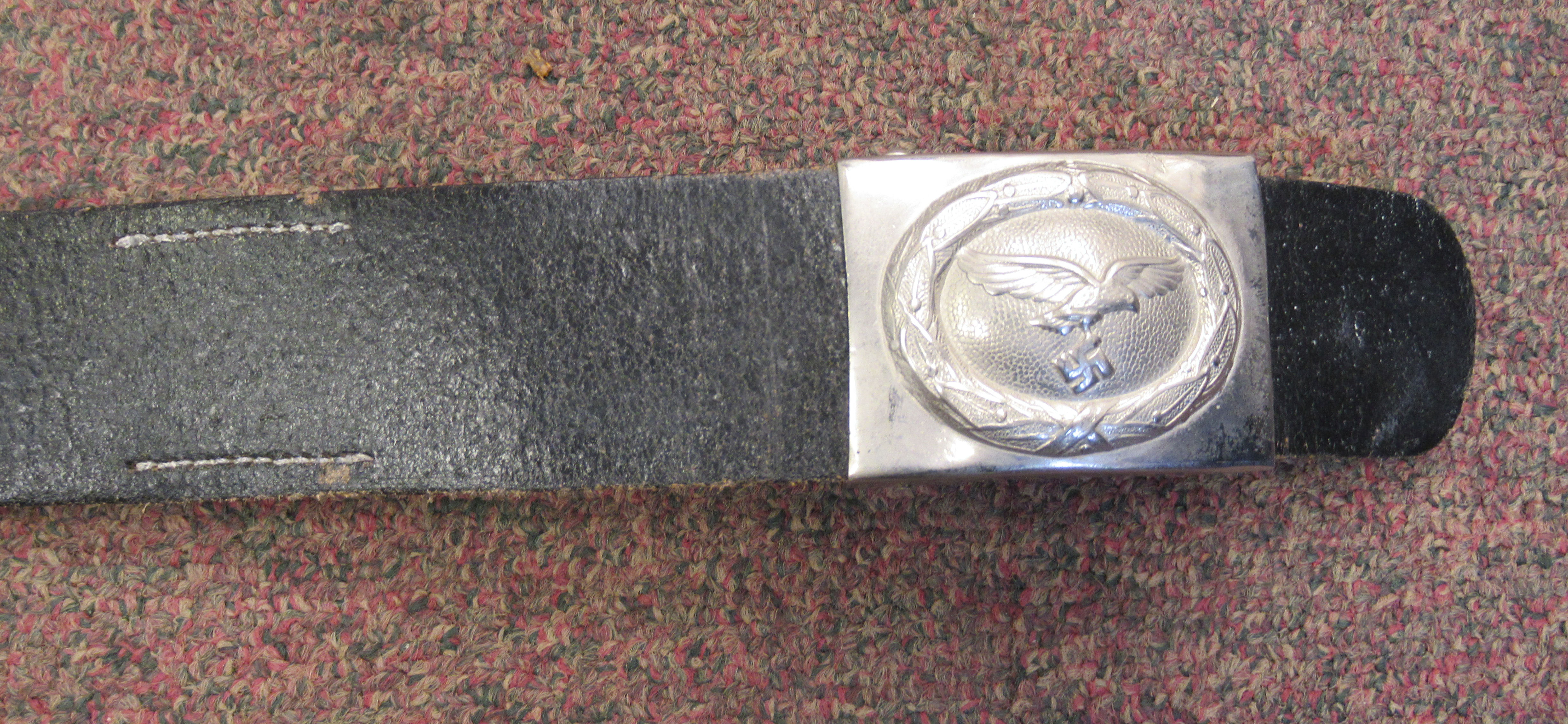 A Third Reich Luftwaffe black hide belt with an impressed weathered spreadeagle emblem, on the white - Image 2 of 5