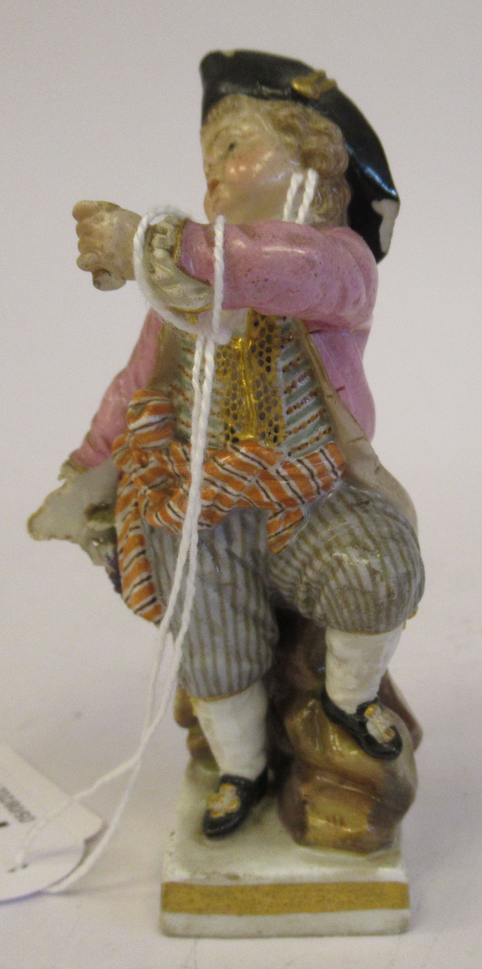 """A 19th/20thC Meissen porcelain figure, a boy dressed as a pirate, on a square plinth 4""""h"""
