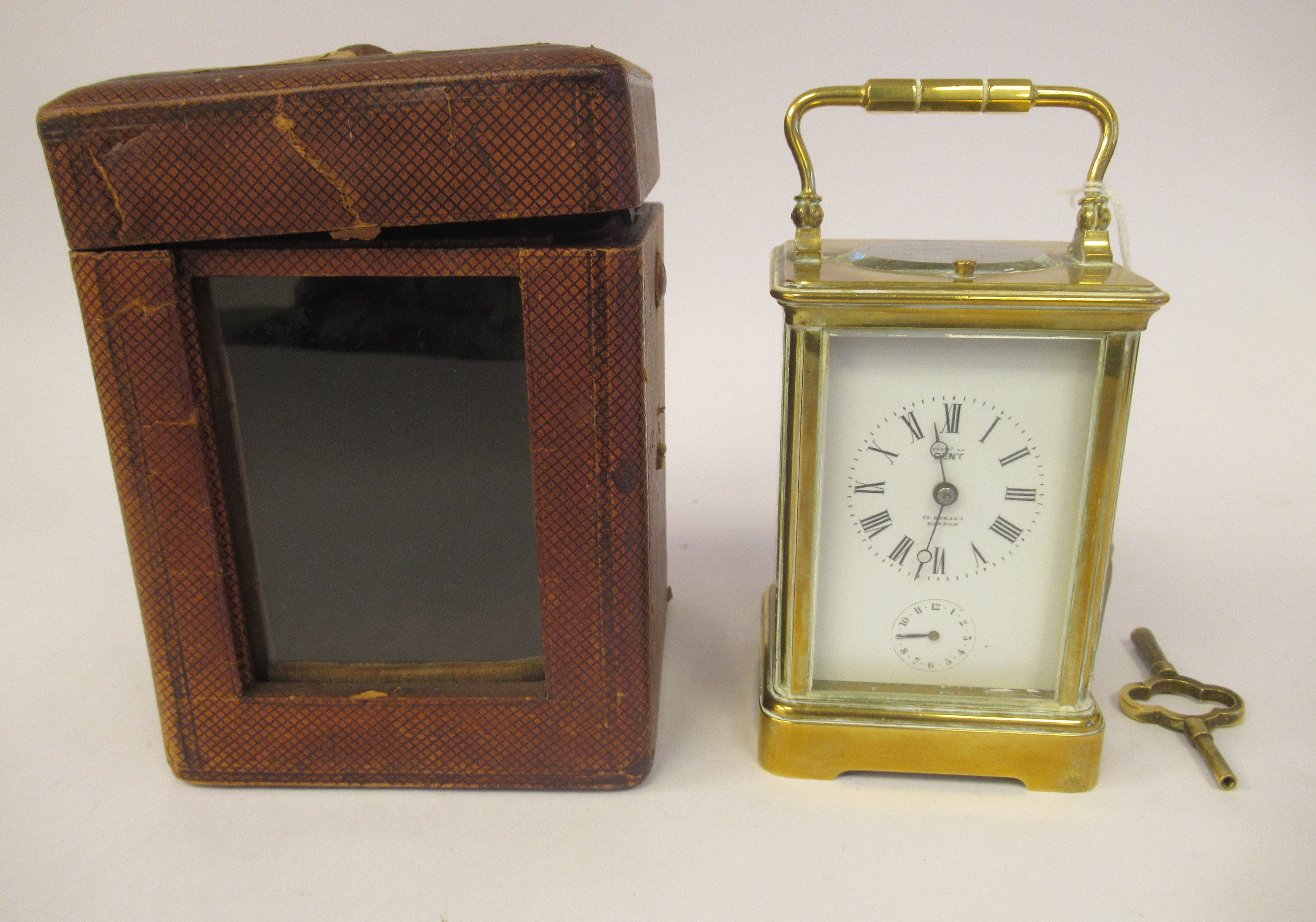 An early 20thC brass cased carriage clock with bevelled glass panels, a folding top handle, on a
