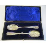 A pair of George III silver Old English pattern berry spoons with impressed, engraved and chased