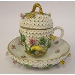 A 19thC Meissen porcelain floral encrusted, single handled cup with a gilded twig finial on the