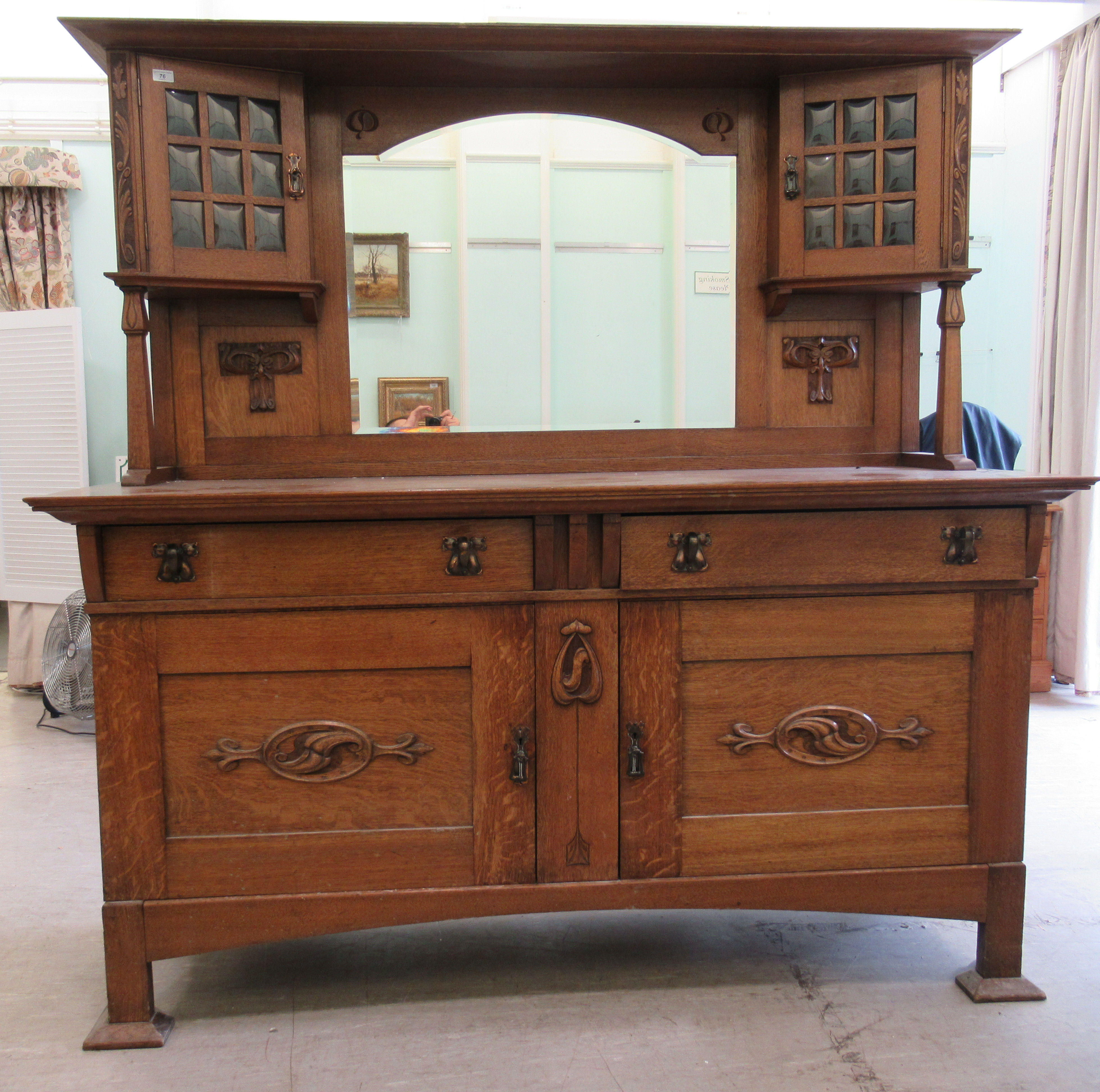An early 20thC Liberty & Co light oak dresser with carved organically inspired ornament, the