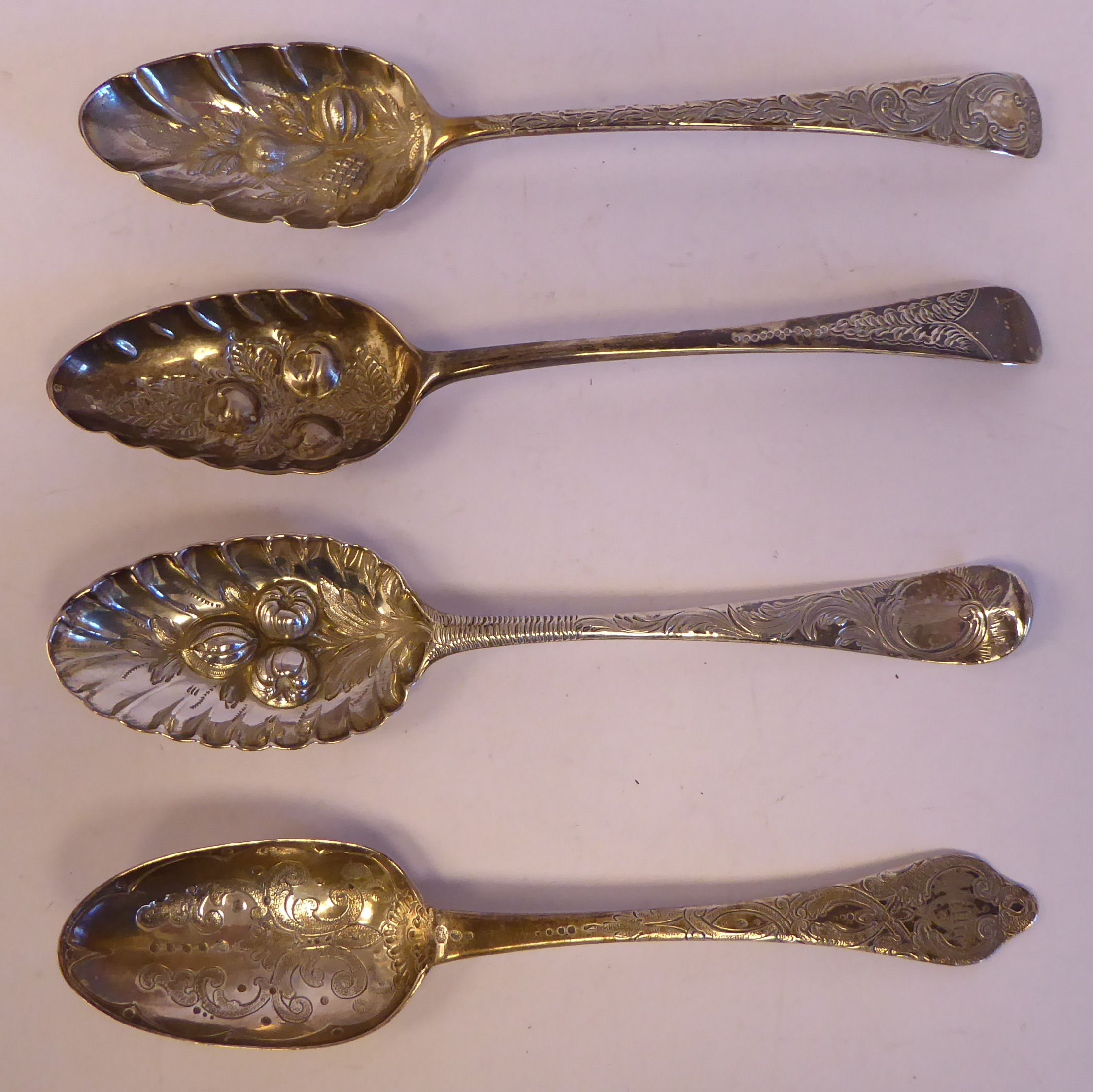 Four similar late 18th/early 19thC variously decorated, silver berry spoonsmixed marks