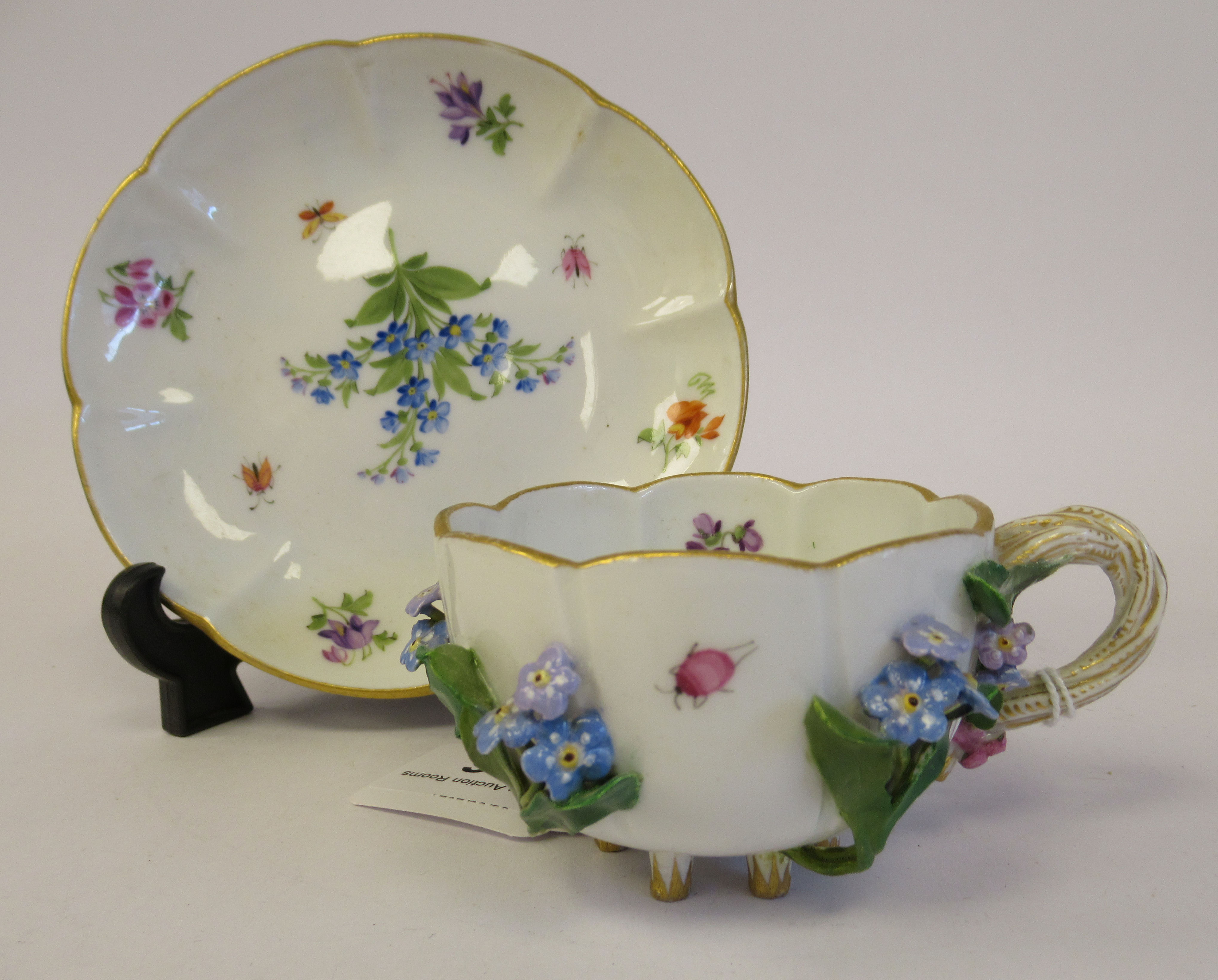 A 19thC Meissen porcelain cup and saucer, having an entwined twig handle, decorated with encrusted