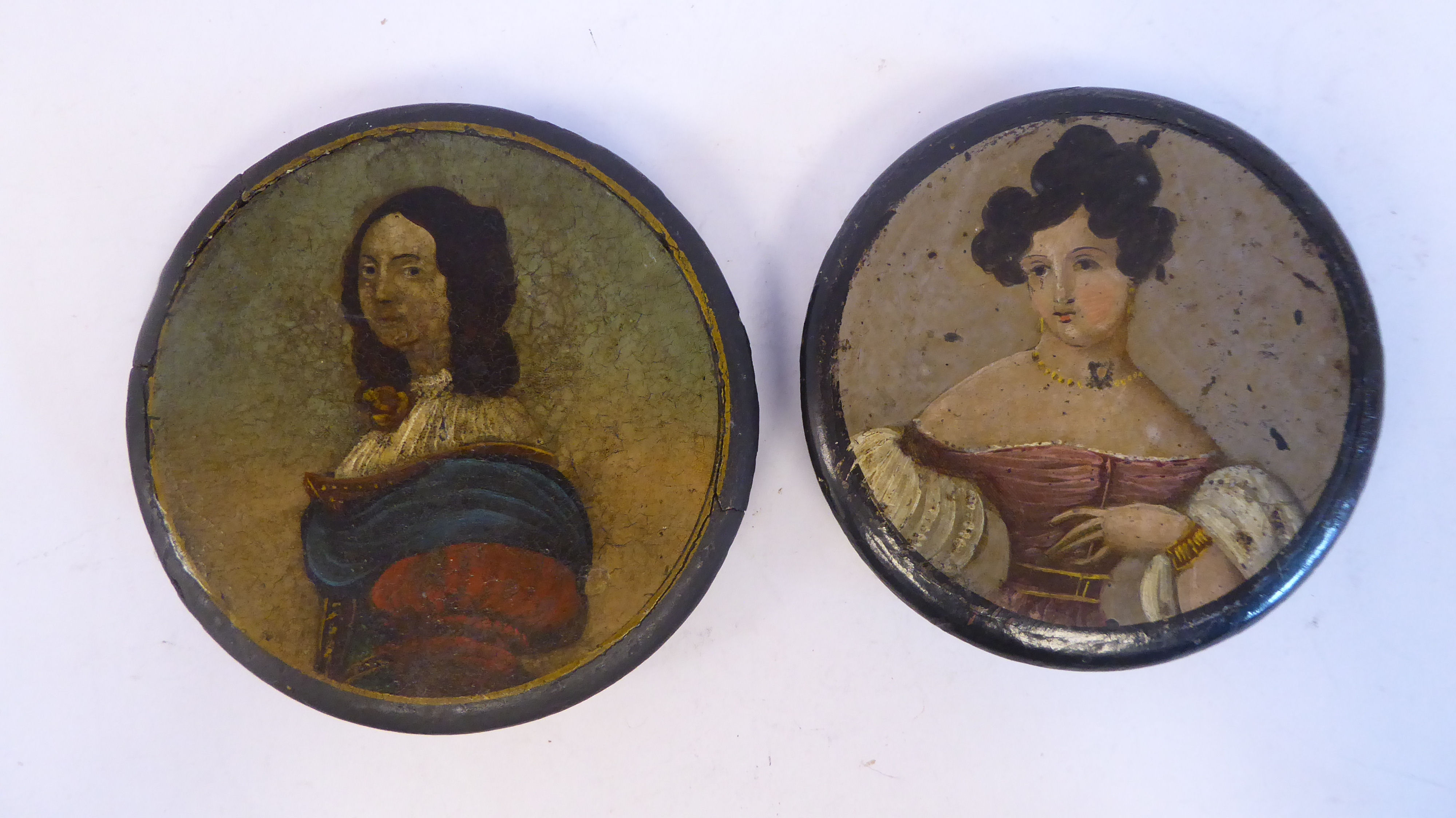 Two similar 18thC black lacquered and overpainted papier mache, shallow snuff boxes, the covers each