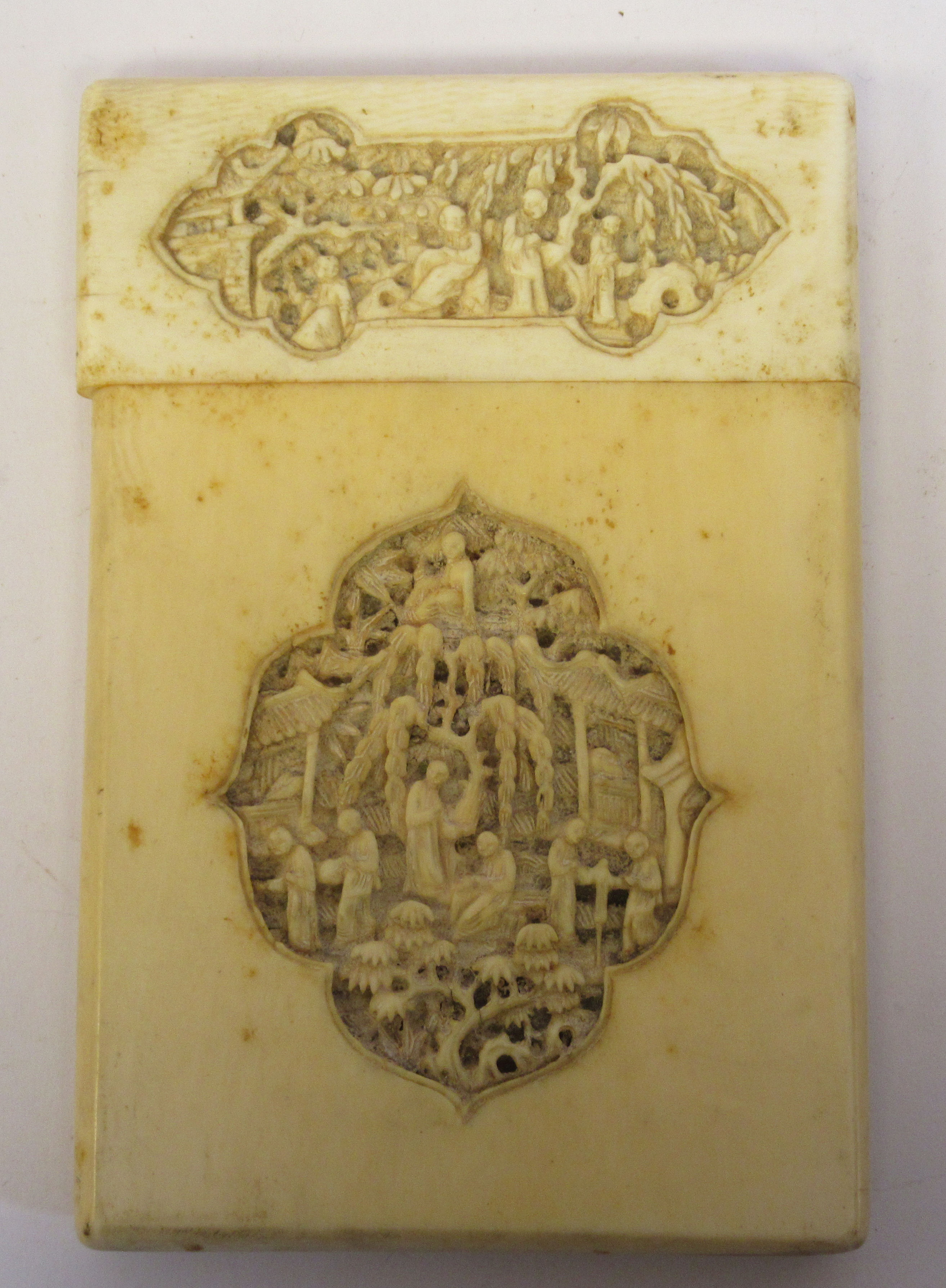 A late 19th/early 20thC Chinese ivory two part card case, carved in vignette panels with figures, in