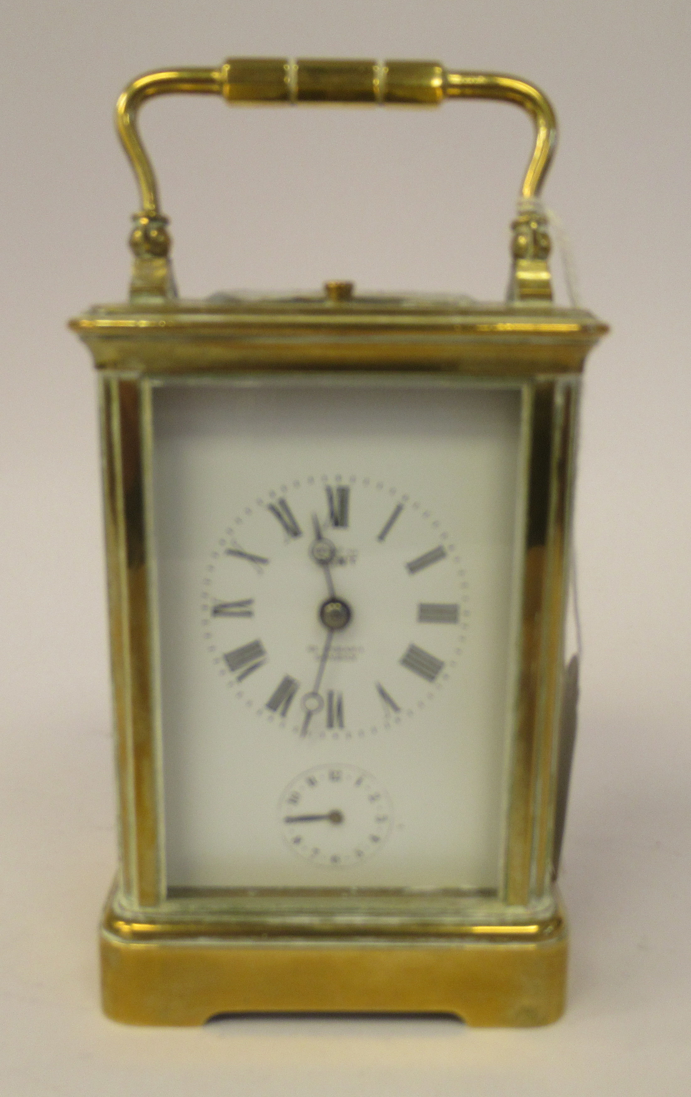 An early 20thC brass cased carriage clock with bevelled glass panels, a folding top handle, on a - Image 2 of 9