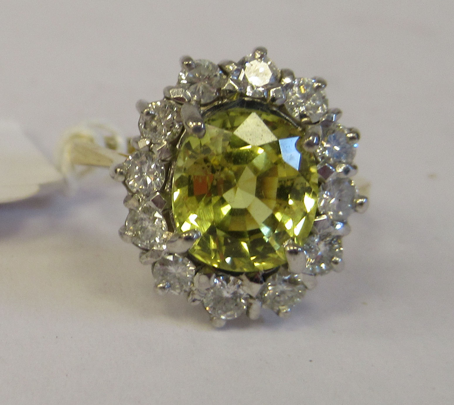 An 18ct gold cluster ring, claw set with a mild yellow Ceylon sapphire, set within a twelve stone