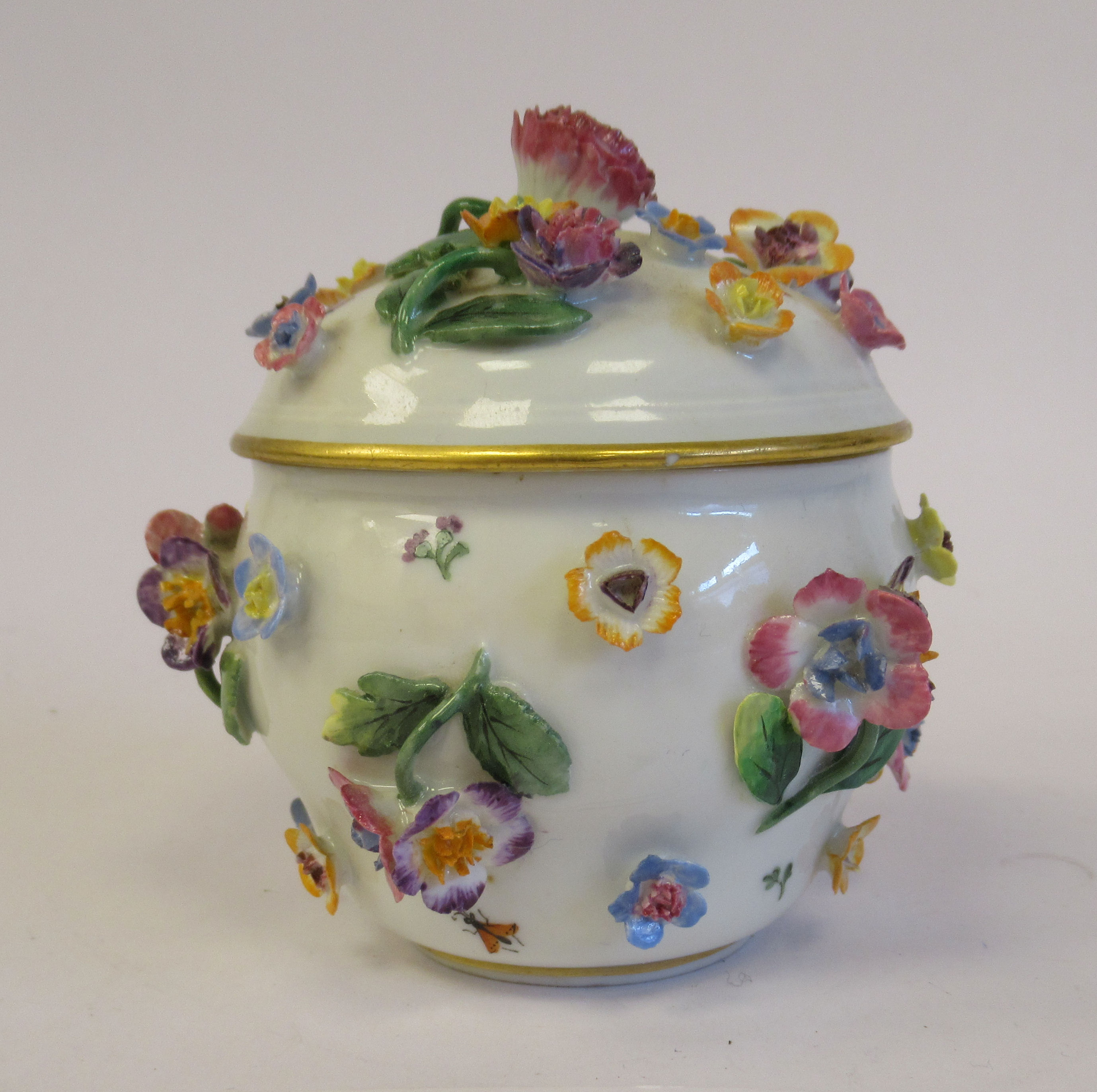 A 19thC Meissen porcelain bulbous pot and domed cover, decorated with encrusted flora and painted