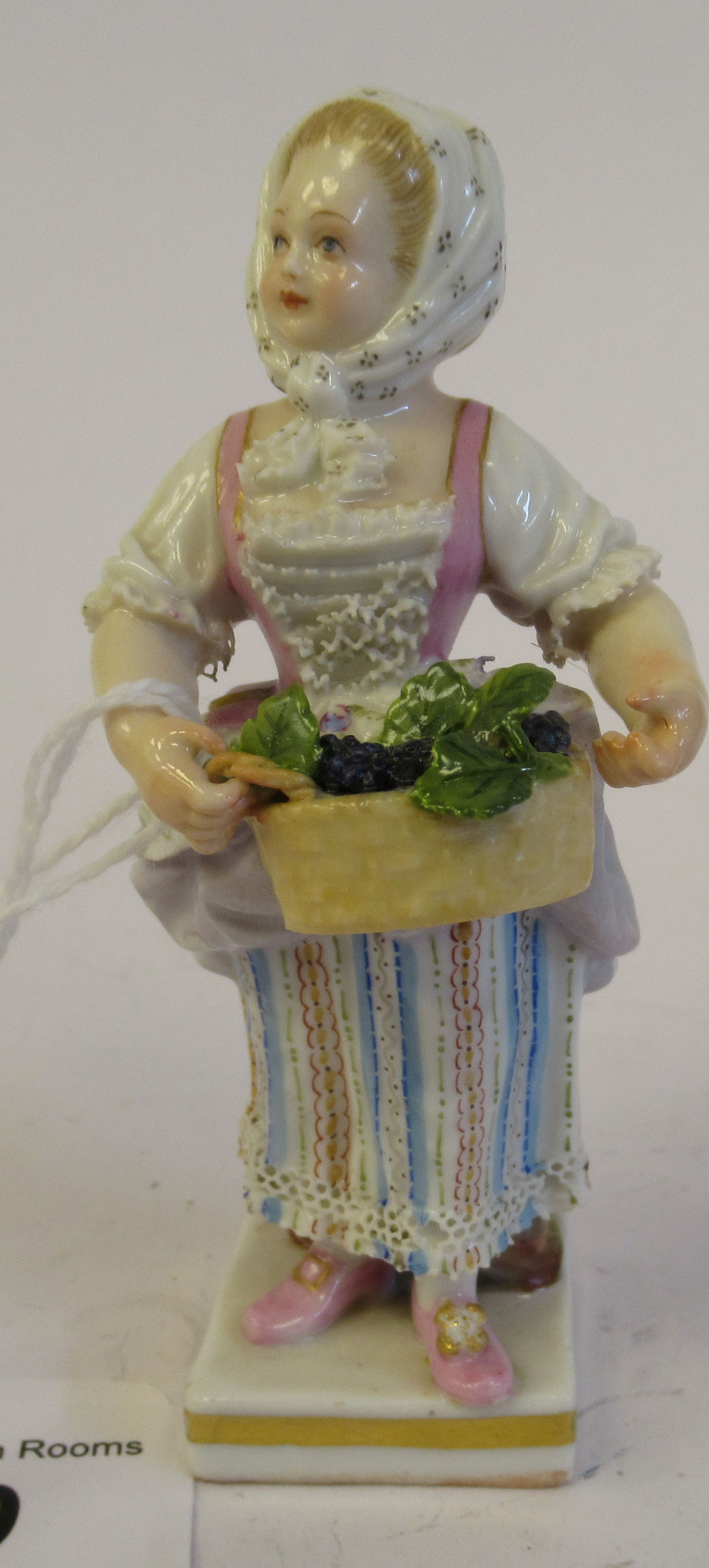 A 19th/20thC Meissen porcelain figure, a girl wearing a floral skirt, carrying a basket of grapes,