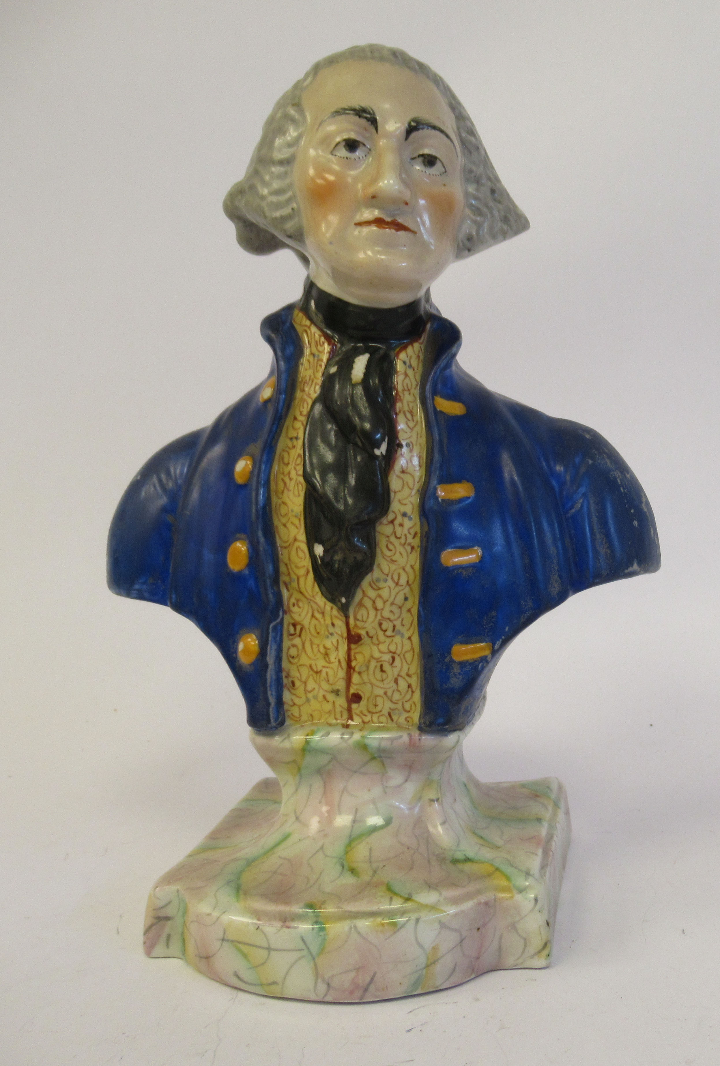 A 19thC Staffordshire pottery bust, featuring a bewigged gentleman, wearing a coat and cravat, on an
