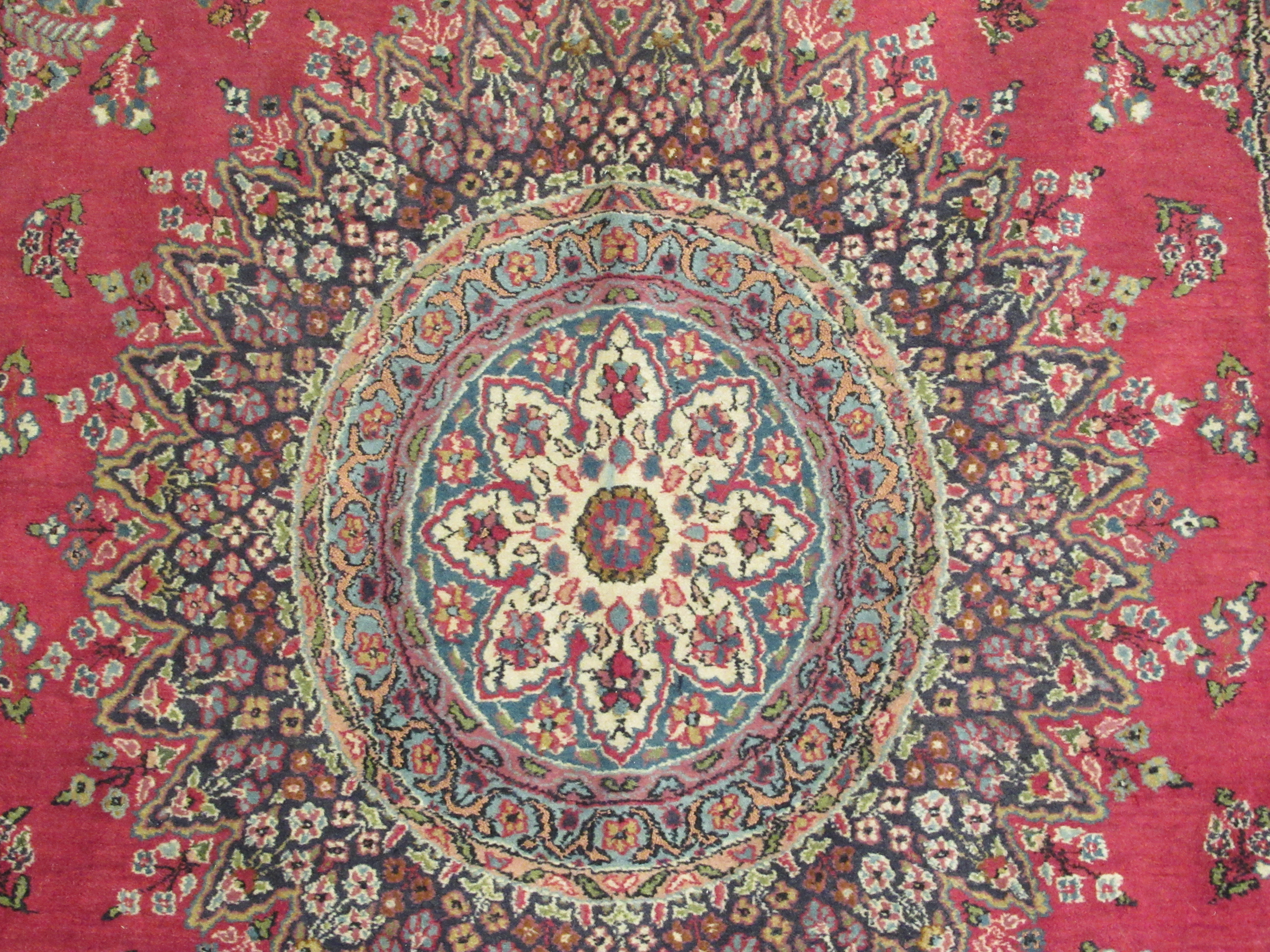 A Persian rug, decorated with a central starburst design medallion, bordered by floral designs, on a - Image 2 of 4