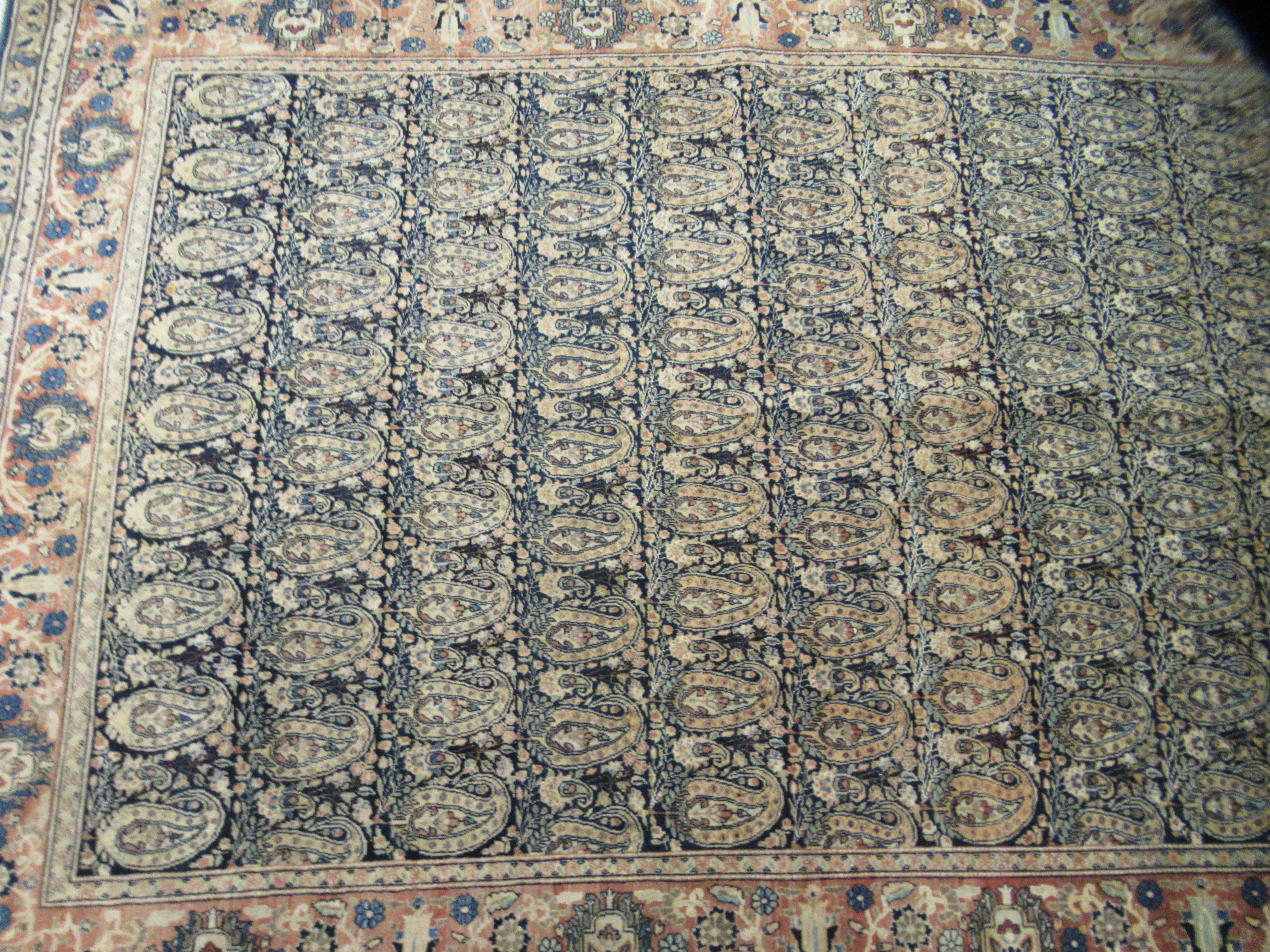A Persian rug decorated with repeating stylised designs, bordered by floral and foliage, on a - Image 2 of 4