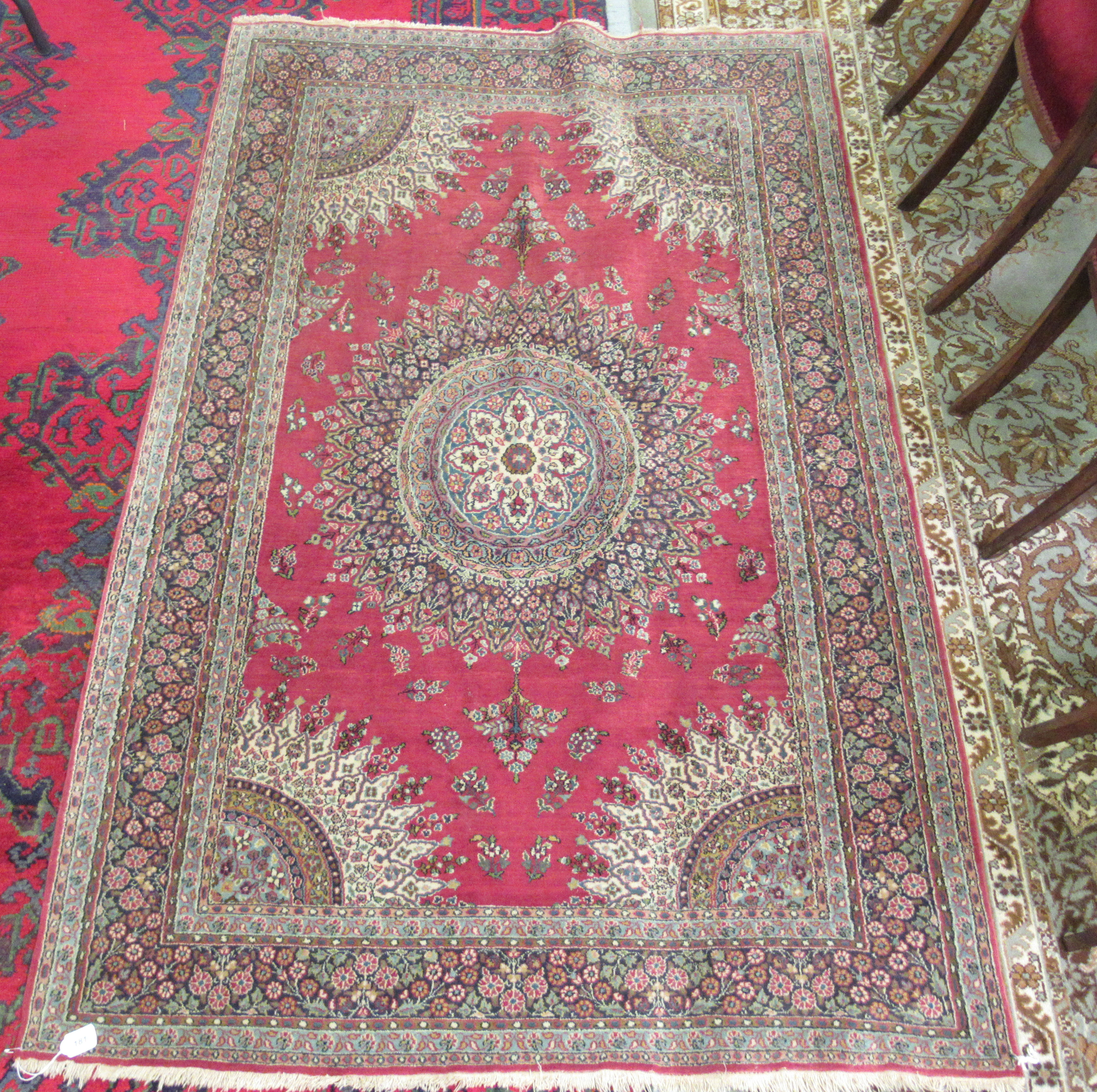 A Persian rug, decorated with a central starburst design medallion, bordered by floral designs, on a