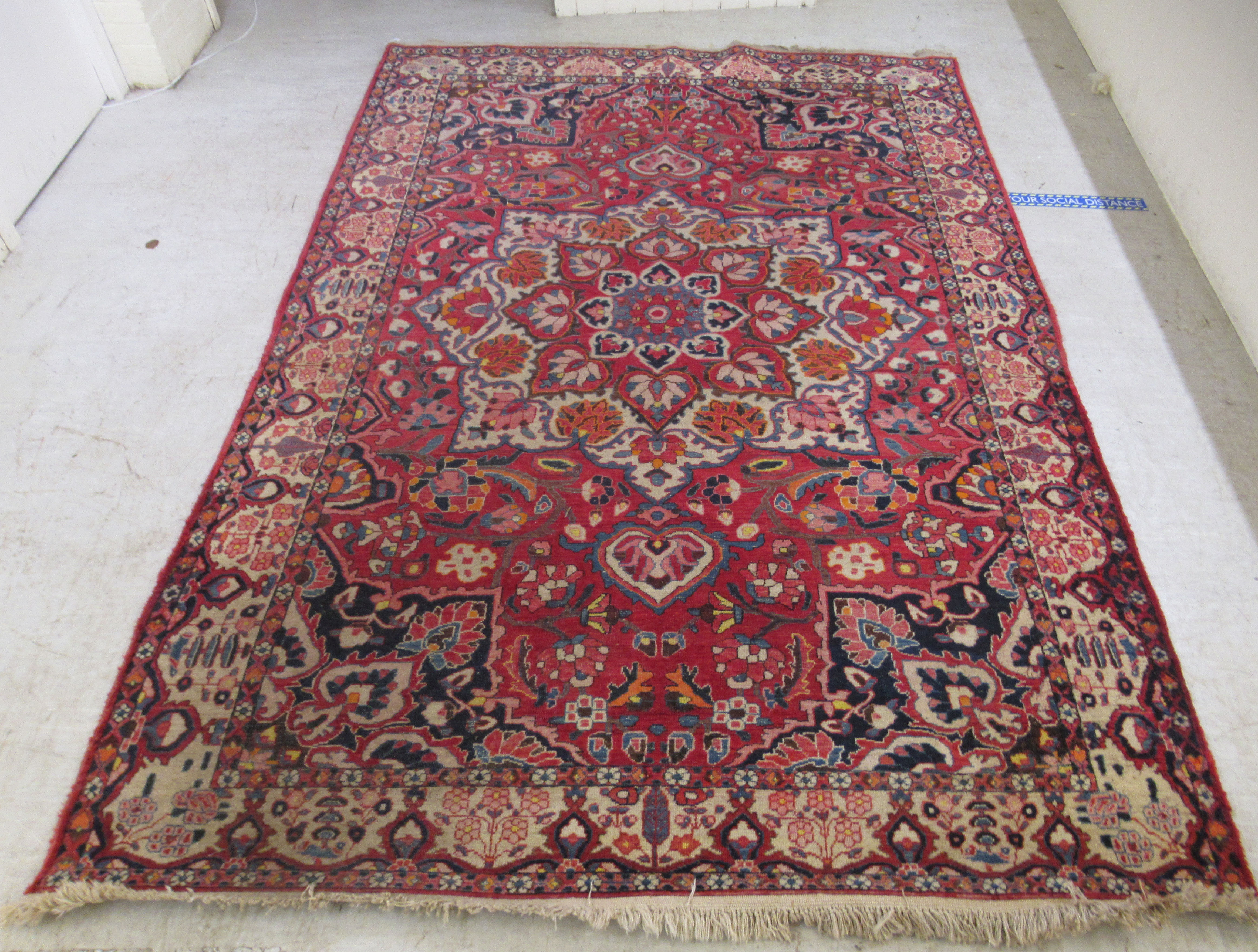 A Persian carpet, profusely decorated with flora and other designs, on a multi-coloured and red