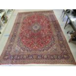 """A Keshan carpet, profusely decorated with floral designs in bright colours, on a red ground 120"""""""