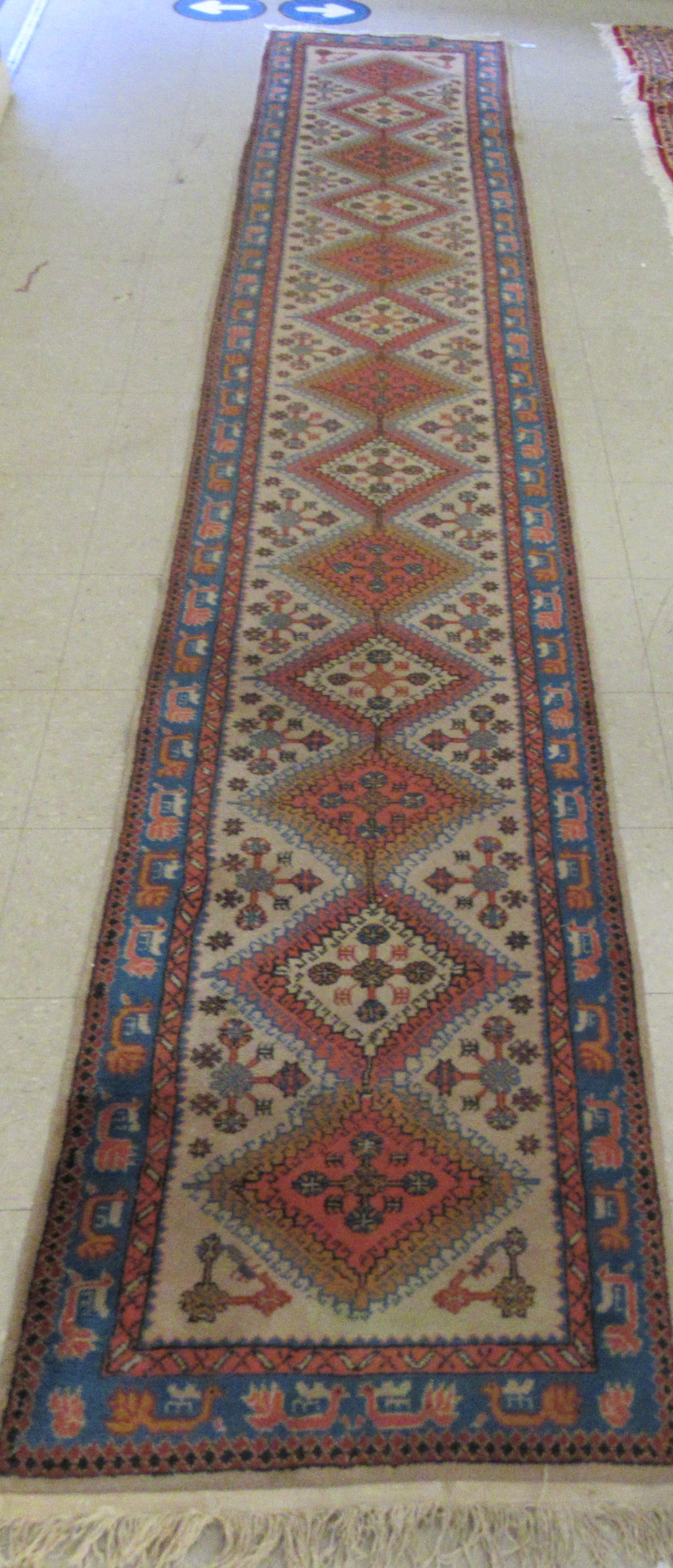 A Samarkand runner, decorated with repeating diamond formations, bordered by stylised designs, on