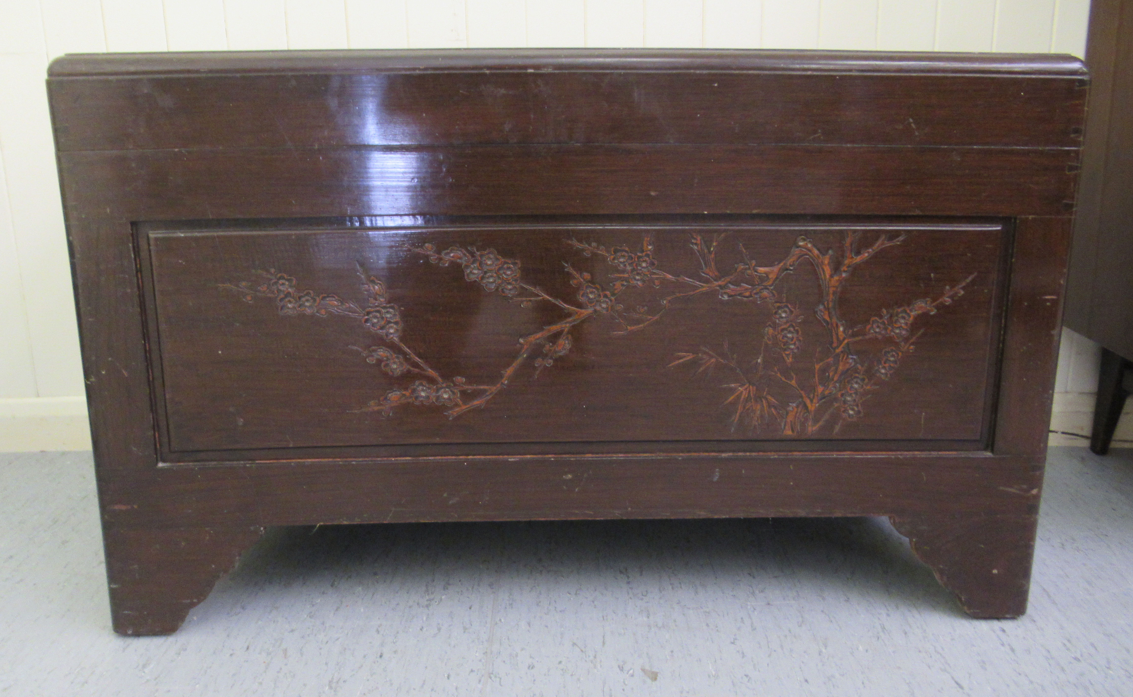 A mid 20thC Chinese carved camphorwood chest, having straight sides and a hinged lid, raised on