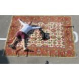 An Indian Agra carpet, decorated in bright colours with stylised floral designs, on a multi-coloured
