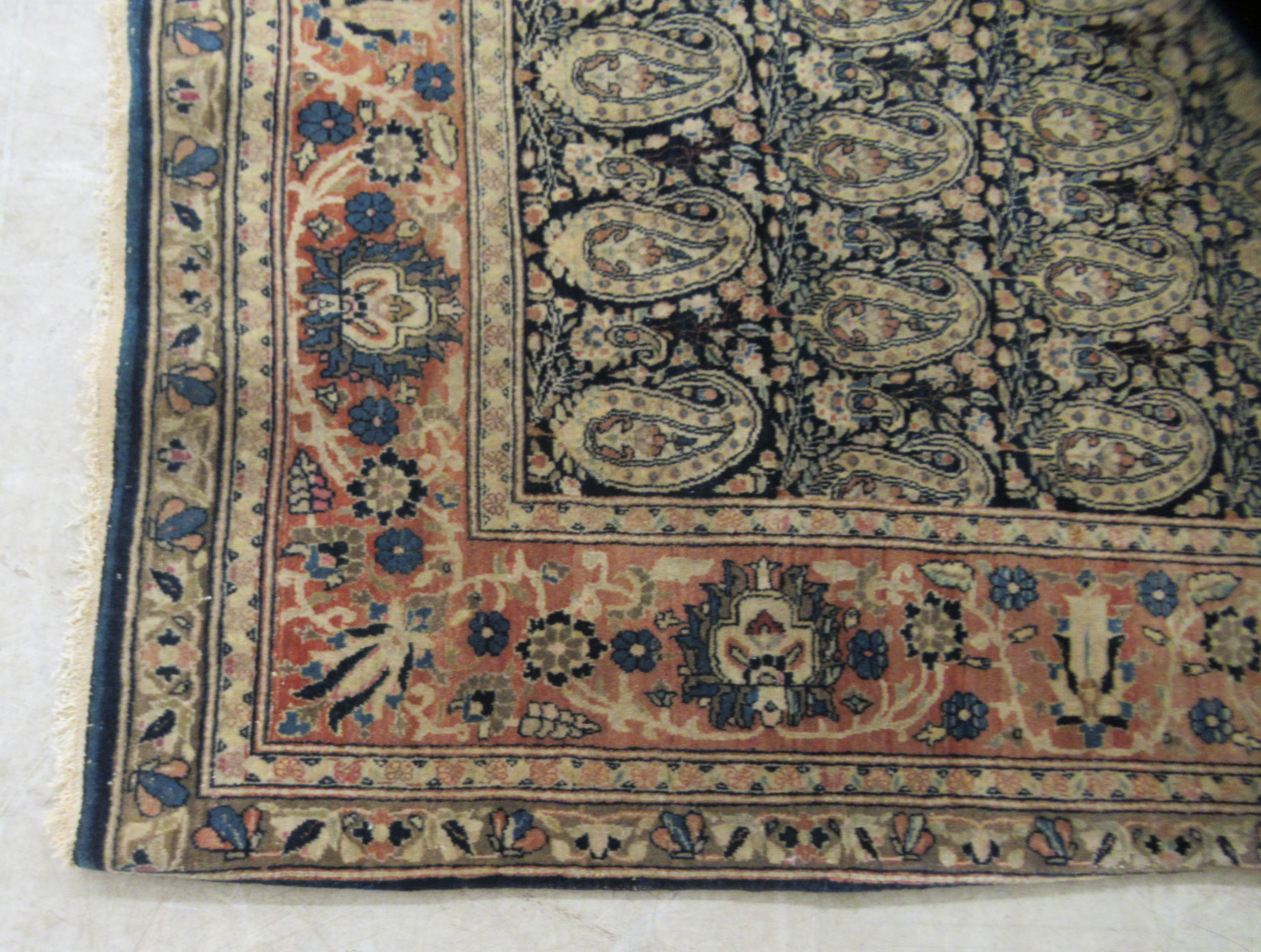 A Persian rug decorated with repeating stylised designs, bordered by floral and foliage, on a - Image 3 of 4