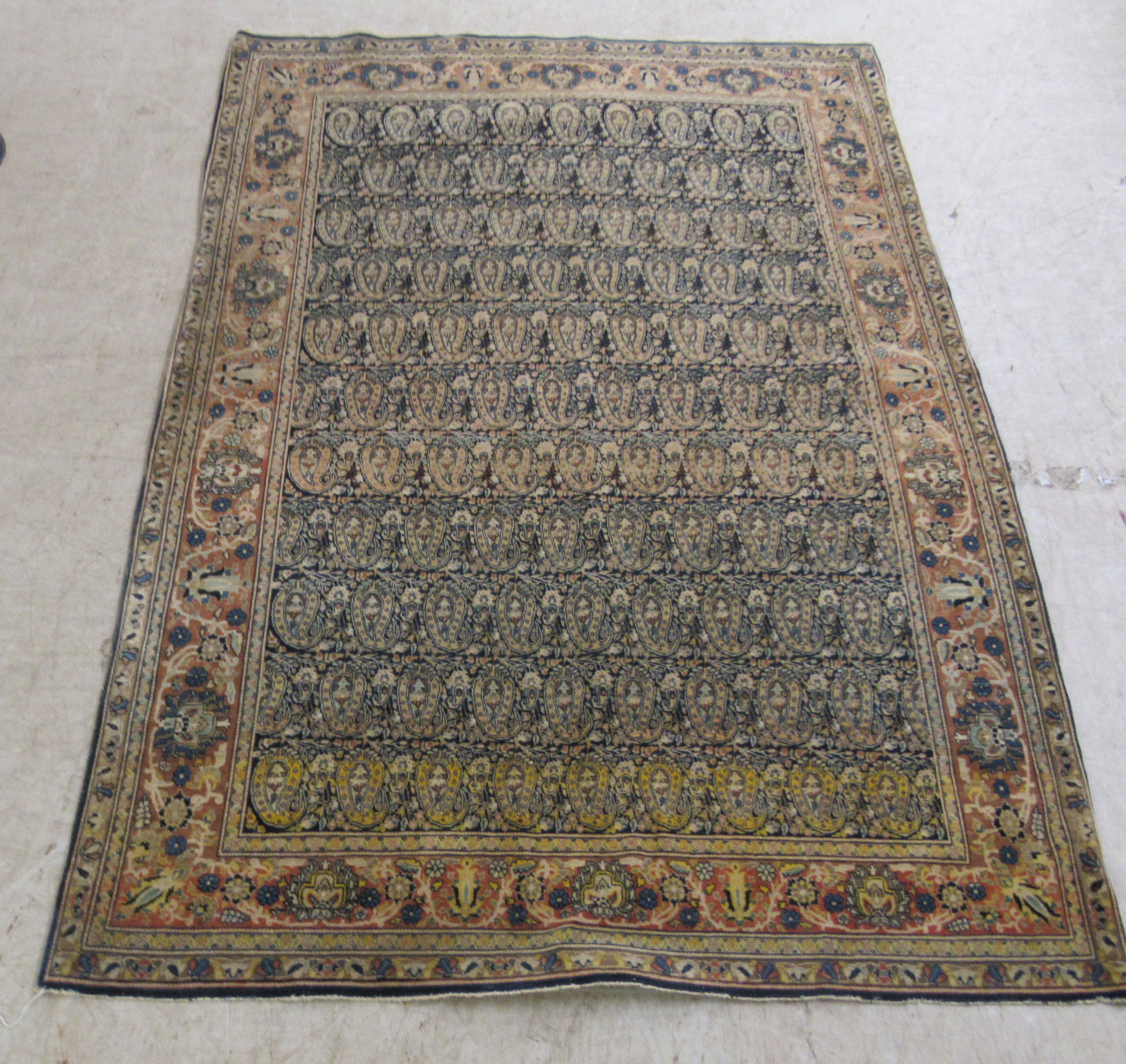 A Persian rug decorated with repeating stylised designs, bordered by floral and foliage, on a