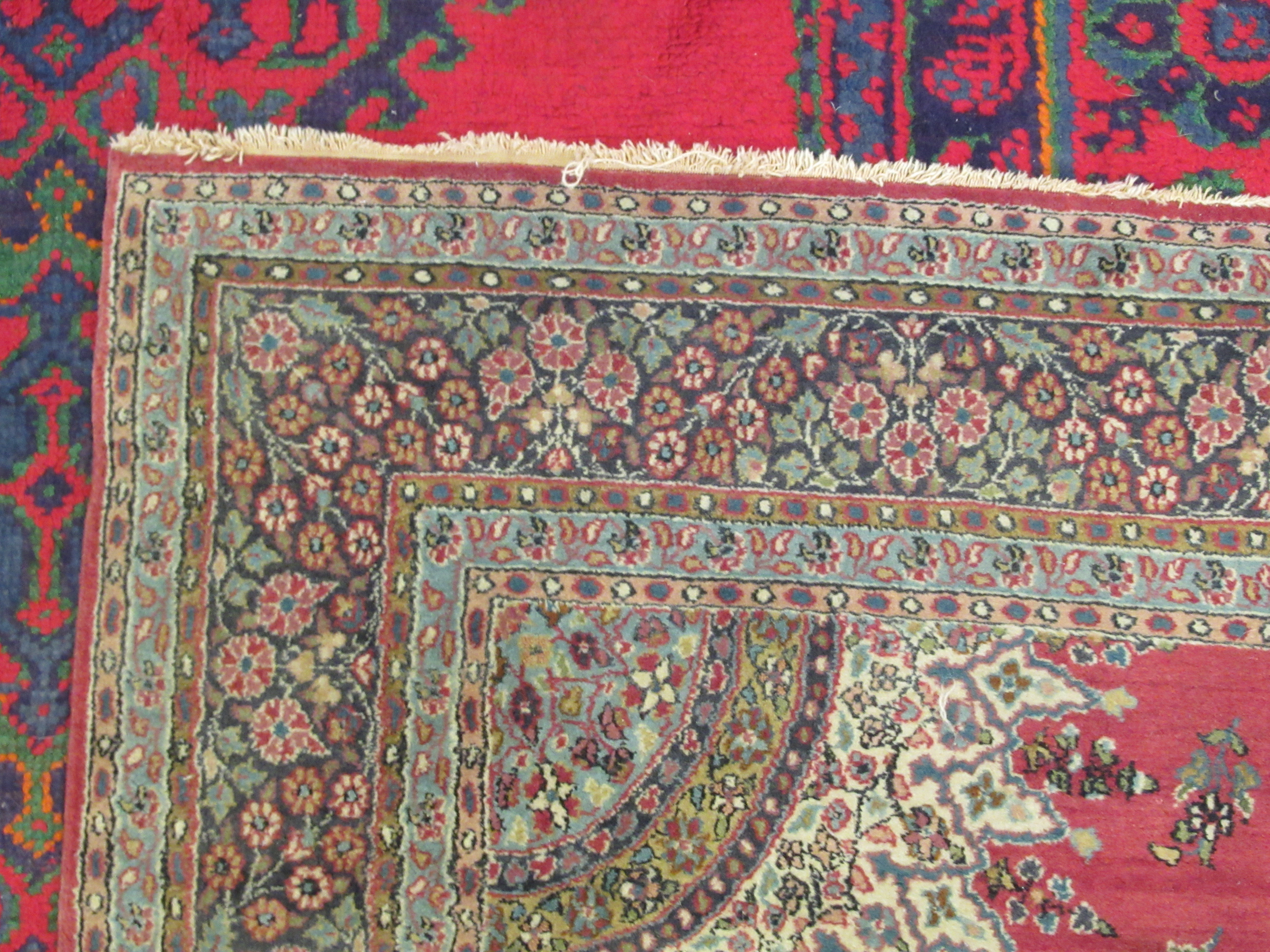 A Persian rug, decorated with a central starburst design medallion, bordered by floral designs, on a - Image 3 of 4