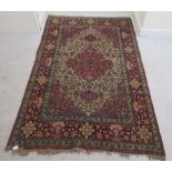 A Persian rug, decorated with a serpentine outlined medallion, bordered by stylised designs on a