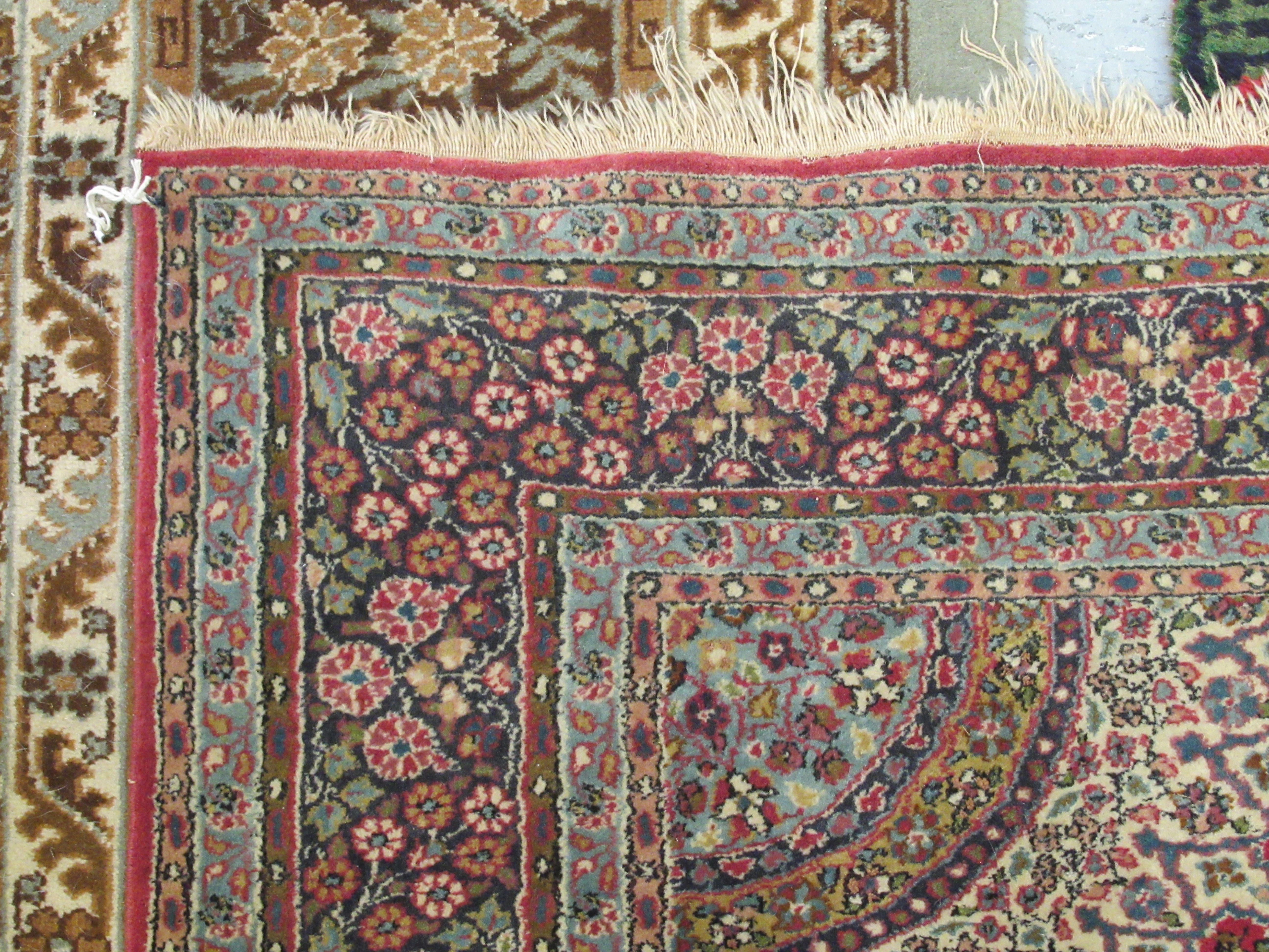 A Persian rug, decorated with a central starburst design medallion, bordered by floral designs, on a - Image 4 of 4